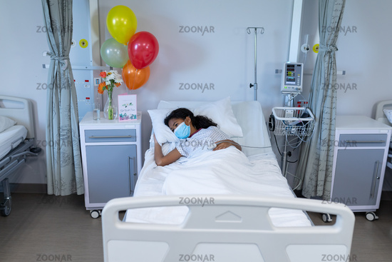 Mixed race sick girl lying in hospital bed wearing face mask and fingertip pulse oximeter