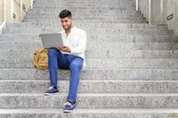 handsome young man working with laptop on stairs