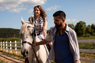The young man helps a woman to ride a horse