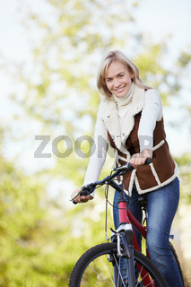 A young girl on a bicycle in the park