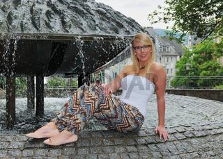 junge blonde Studentin sitzt auf dem Brunnen des Marktplatz in Siegen