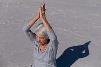 Senior Caucasian woman meditating at the beach.