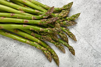 Fresh green asparagus on stone table surface