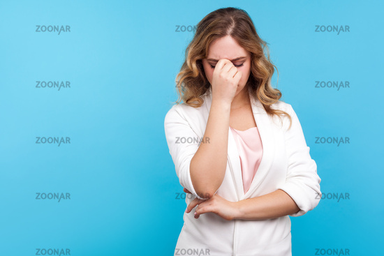 Portrait of emotional woman in jacket on blue background.