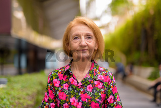 Portrait of a senior woman thinking outdoors during summer