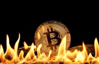 Gold bitcoin physical coins in fire flames