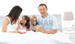 Happy dad having breakfast with his family on his bed