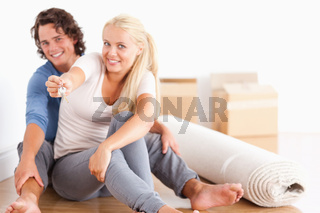 Woman sitting with her boyfriend giving keys