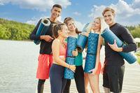 Gruppe Freunde beim Yogakurs am See mit Yogamatte