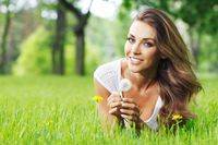 Woman lay in park with dandelion
