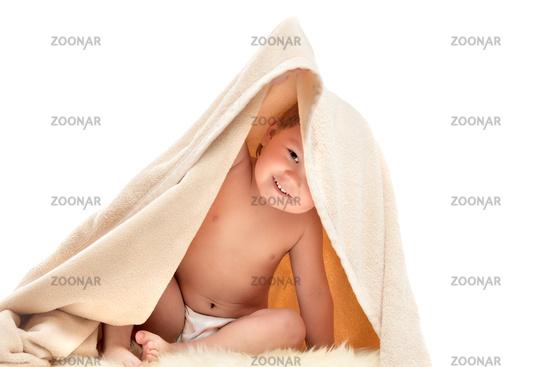 small child plays under beige towel