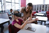 African american female teacher teaching caucasian girl to use vr headset in the class at school