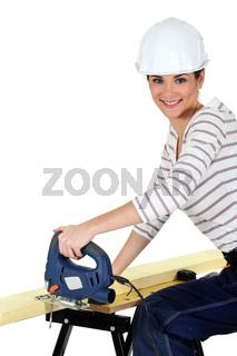 Woman cutting wood with a jigsaw