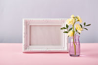 Flower of yellow matthiola in little glass vase with white photo frame. Design concept of holiday greeting on pink table