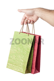 male hand holding two shopping bags isolated on white background