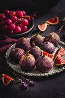 Organic fresh figs with red grapes and lavender on dark background