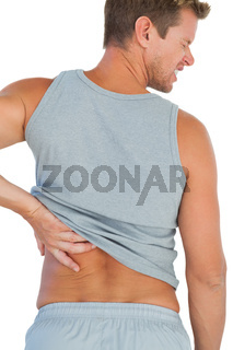 Man in tank top rubbing his back because of a back pain