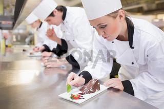 Chef's team garnishing slices of cake