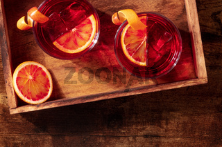Negroni cocktail with blood oranges, overhead shot on a wooden background