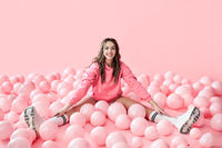 Young trendy woman posing with pink ballons on pink background