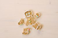 Gingerbread man with severed legs and arms. The limbs of the cookie are separated from the body. Christmas gingerbread on a white wooden background.