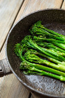 Fresh broccolini with nut powder baked close up