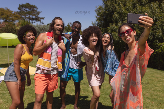 Diverse group of friends taking selfie at a pool party