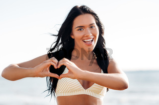 smiling young woman in showing hand heart on beach