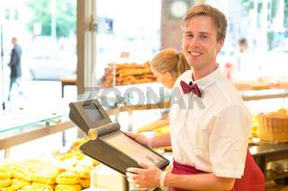Kassierer in Bäckerei posiert mit der Kasse