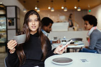 Female student using smartphone while sitting in cafe