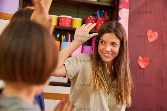 Kindergärtnerin macht High Five zur Begrüßung mit Kind