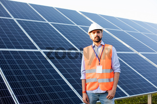 The young engineer stands at a solar station