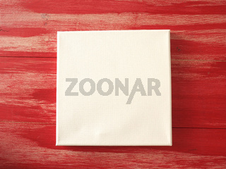 Invitation concept with a blank canvas on a red wooden background