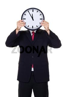 Manager im Stress mit Uhr vor Kopf.