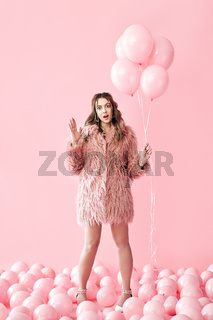 Full length portrait of funny trendy woman with pink balloons on pink pastel background