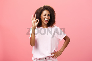 Girl got us covered. Charming charismatic and confident african american skillful woman in stylish outfit holding hand on waist showing okay gesture and winking assured at camera over pink wall