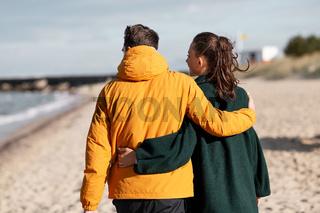 couple walking along autumn beach