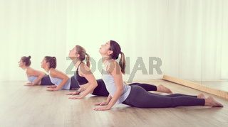 Group of young sporty sexy women in yoga studio, practicing yoga lesson with instructor, forming a line in asana pose. Healthy active lifestyle, working out indoors in gym