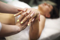 Woman masseur giving hand massage to client