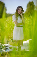 Young blonde woman in white dress is kneeling on a picnic sheet in tall grass.