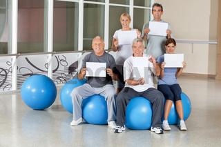 Senioren im Fitnesscenter halten Schilder