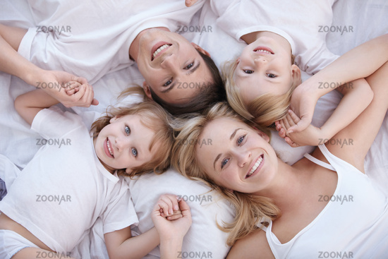 Smiling family lie on a white bed