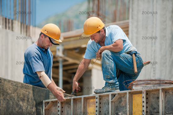 Two construction workers installing concrete formwork frames
