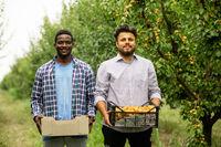 Happy multiracial family in their fruit garden
