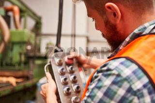 Arbeiter bedient Knöpfe an der Steuerung einer Maschine