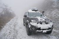 SUV on rise of snow winter forest