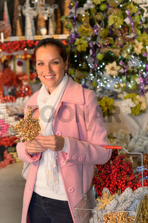 Smiling woman shopping Xmas decorations in shop