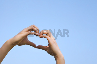heart shape hand sign or love gesture against clear blue sky