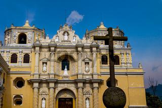 The facade of the 'La Merced' church with stone cross in Antigua, Guatemala