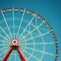 Ferris wheel attraction on blue sky background.